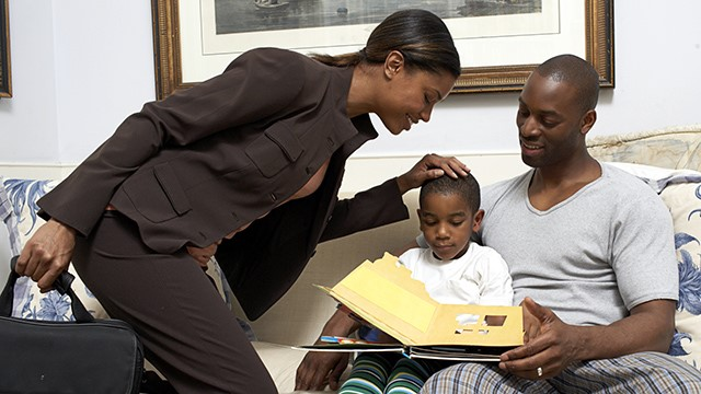 Woman in suit looking at man and child reading a book