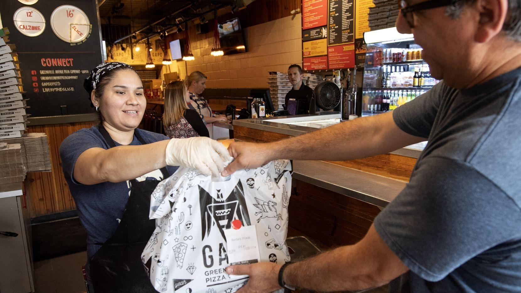 Restaurant worker handing over takeout bag